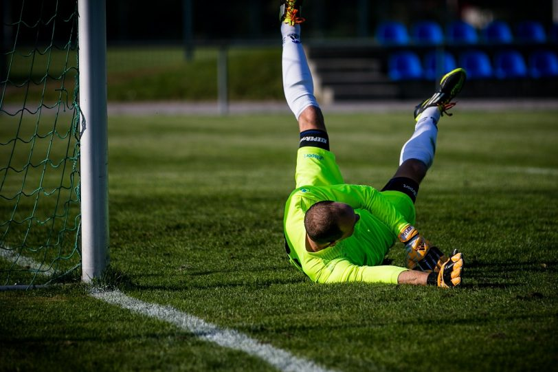 Goalkeeper diving for the ball, representing an employer failing to recruit an IT person because they were too slow.