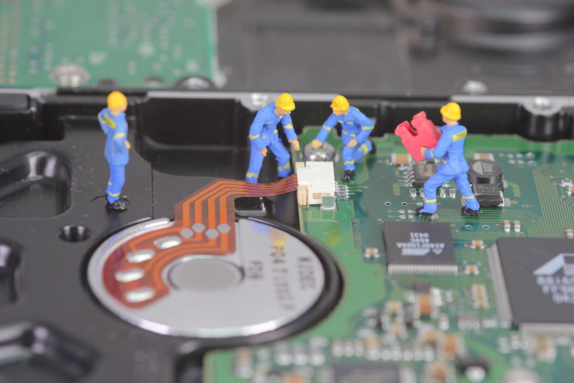 In-House IT vs Outsourcing IT - little men working on hardware